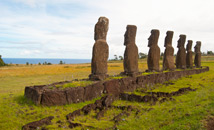 Ahu Akivi moai statues facing ocean with crematorial pits behind monument