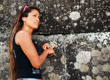Rapa Nui girl showing a triangular rock fitting in Ahu Tahira.