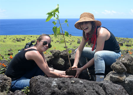 Happy women planting tree, reforesting Easter Island.
