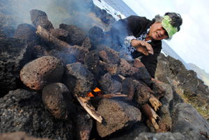 Native Rapa Nui preparing fire for cooking fish at Easter Island