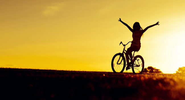 Girl on bicycle at sunset