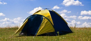 Camping tent with grass and blue sky with white clouds