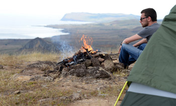 Man looking into campfire with tent, camping at top of Poike.
