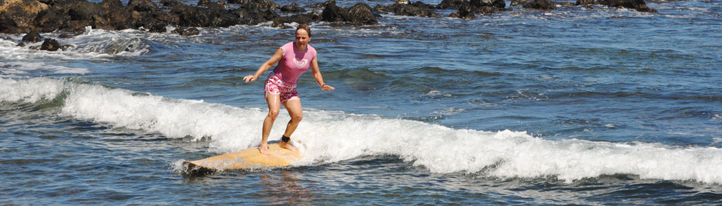 Woman learning wave surfing in Rapa Nui